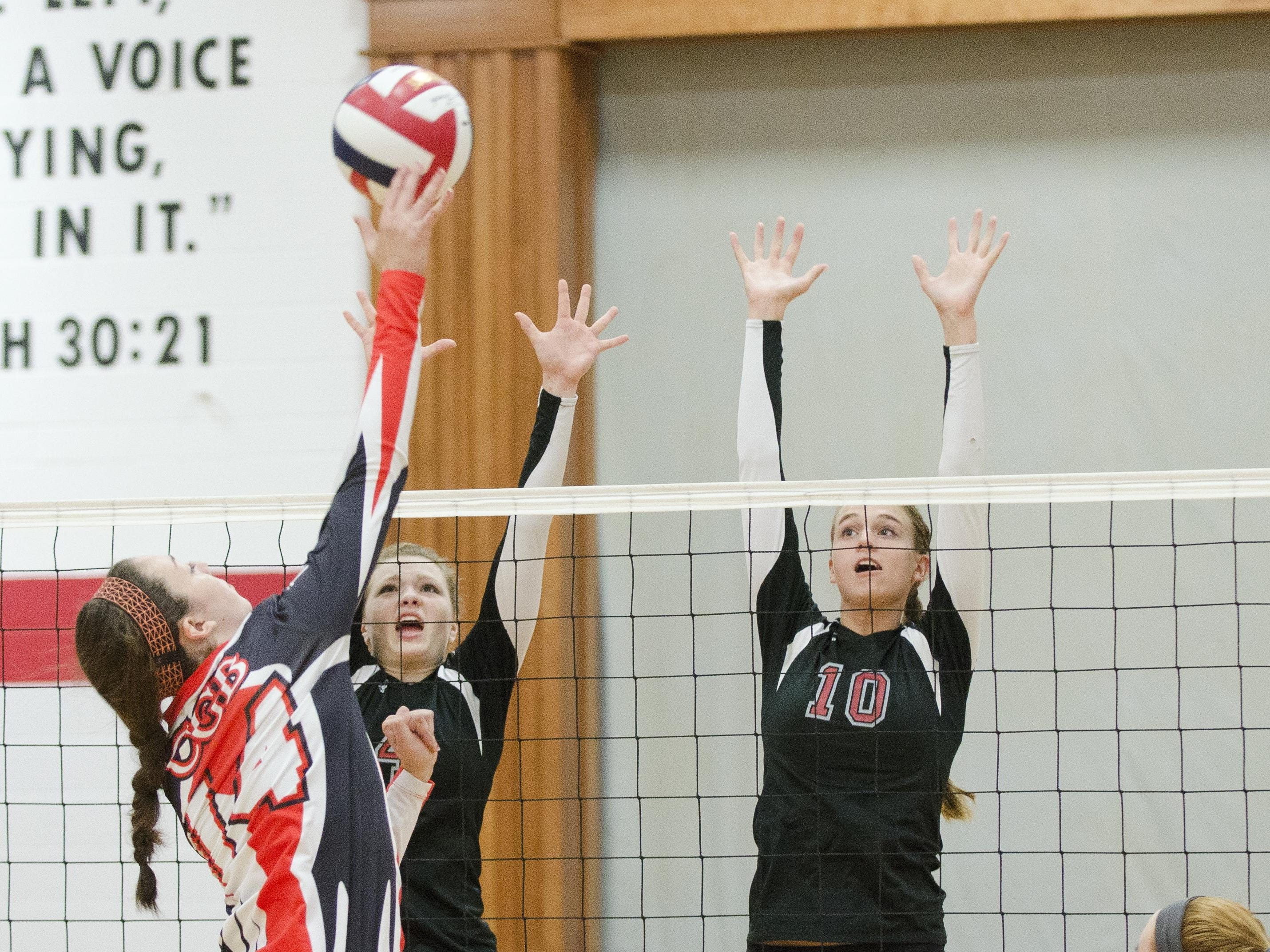 Cedar Grove-Belgium's Ashely Voskuil (14) hits a ball over Manitowoc Lutheran's Emma Dewane (4) and Lindsay Engelbrecht on Tuesday night.