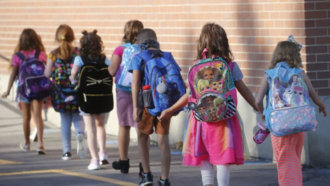 Young students walk into a school in this file photo.