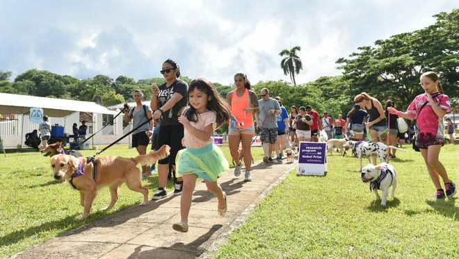 Event goers guide their dogs during the 5th Annual American Cancer Society Bark For Life opening lap at the Plaza de España on Sept. 3, 2017.