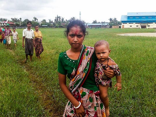 A woman holds a child in her arms as she arrives at the Yathae Taung township in Rakhine State in Myanmar after fleeing from violence in their village on August 26, 2017.