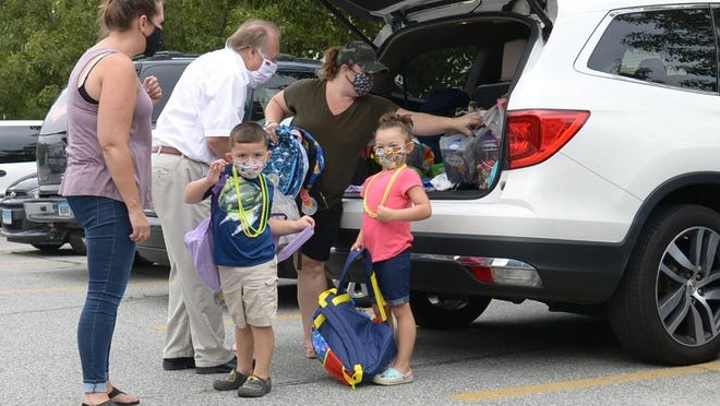 Jacson Newland, age 3, left, and Kennadie Newland, age 5, of Moosup, arrive Saturday at Plainfield Town Hall with donations of backpacks and school supplies for Project PIN food pantry.