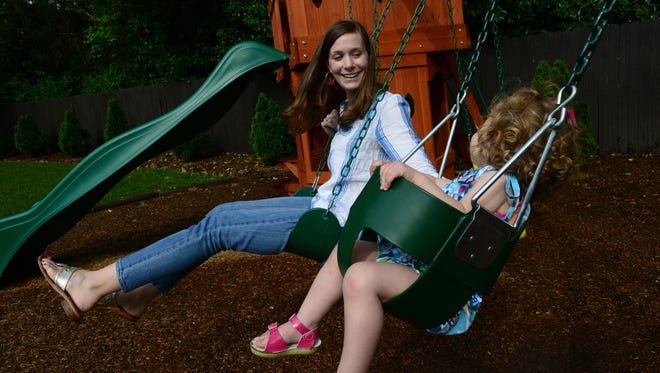 Lindsey Motley swings with her daughter Lilla on their backyard playset.