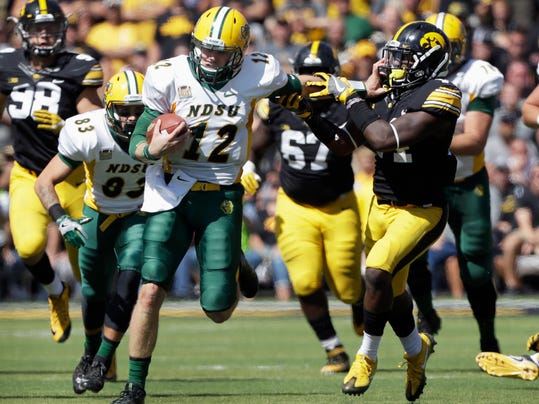 FILE - In this Sept. 17, 2016, file photo, North Dakota State quarterback Easton Stick (12) tries to break a tackle by Iowa's Desmond King during an NCAA college football game in Iowa City, Iowa. North Dakota State won 23-21. North Dakota State faces San Diego Saturday, Dec. 3, 2016, in Fargo in their run for a sixth straight national title. (AP Photo/Charlie Neibergall, File)