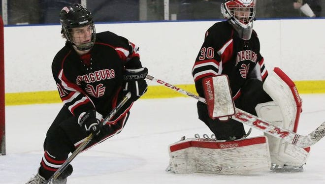 De Pere's Brennan Bockin (11) looks to move the puck while goalie Brett Geurts (30) observes during Wednesday's game against Sheboygan at the Lakers Ice Center in Sheboygan.