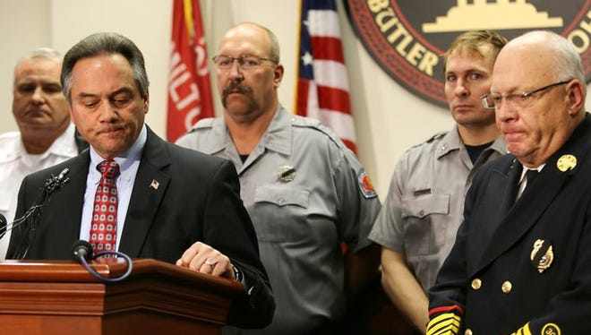 Flanked by members of the City of Hamilton Fire Department, city Safety Director J. Scott Scrimizzi (left) speaks to the media at a news conference Monday along with Fire Chief Steve Dawson (far right).