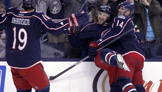 Columbus Blue Jackets' Ryan Johansen (19), Nick Foligno  and Blake Comeau (14) celebrate Foligno's goal against the Tampa Bay Lightning in the second period of an NHL hockey game in Columbus, Ohio, Tuesday, Dec. 3, 2013. Columbus won 1-0.