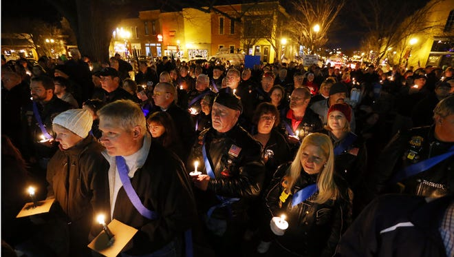 People hold candles while attending the Standing with the Thin Blue Line rally supporting police officers on Friday.