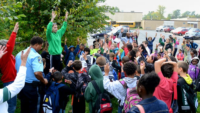Event organizer Kelly Botwinski speaks to the crowd of students and community members before the start of the walk from the Lansing STEM Academy to Lewton Elementary Wednesday as part of National Walk to School Day.