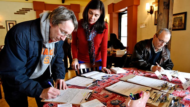 From left, Butch Potter, of York Township, Pennsylvania State Rep. Kristin Phillips-Hill and York Township Commissioner Bob Kessler are shown at a table where numerous petitions await signatures during a petition signing event, held by Phillips-Hill, at Mama's Pizza in Loganville, Saturday, Feb. 13, 2016.
