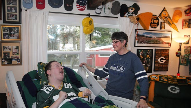 Green Bay Packers football fan Joshua McCall who suffers from cerebral palsy is going to the football game against the Seahawks in Green Bay with his mother Stacey McCall.