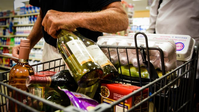 Dave Johnson of Palmyra places bottles of wine in with his groceries as Weis Markets in Palmyra held a grand reopening ceremony to celebrate their recently remodeled store and their newest addition -- a beer and win cafe on Thursday, Sept. 21, 2017.
