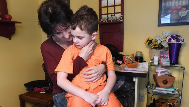 Denise Shanahan gives her 5-year-old grandson some comfort at their home in Stewartstown. He was showing signs of coming down with a cold and was irritable before sitting in her lap. Shanahan has been caring for her two grandsons after her daughter Bryanna overdosed in December 2015.