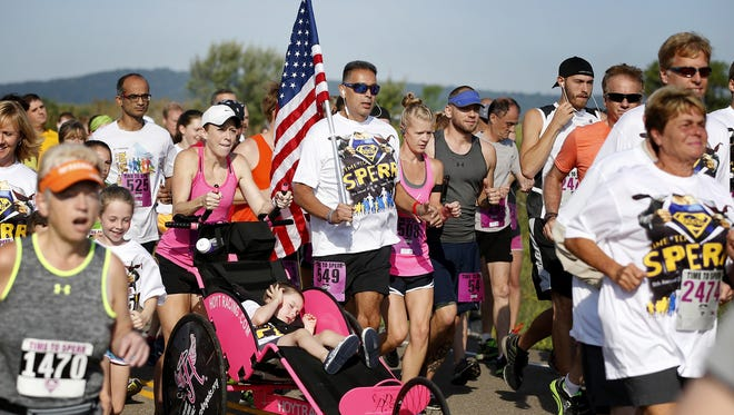 Carrying an American flag, a runner sets pace near the middle of the pack during the August 2016 Time to Sperr run in Big Flats.