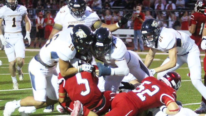 Stephenville defensive players Jace Tummillo (16) and Colton Accomazzo (7) combine to tackle a Salado ball carrier during Friday's football game.