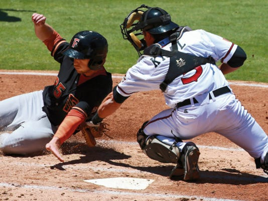 Chihuahuas' catcher Robert Kral tags out sliding Fresno baserunner Alex Presley on Sunday. Presley was trying to score on a double steal, but was nabbed by a throw from second baseman Taylor Lindsey.