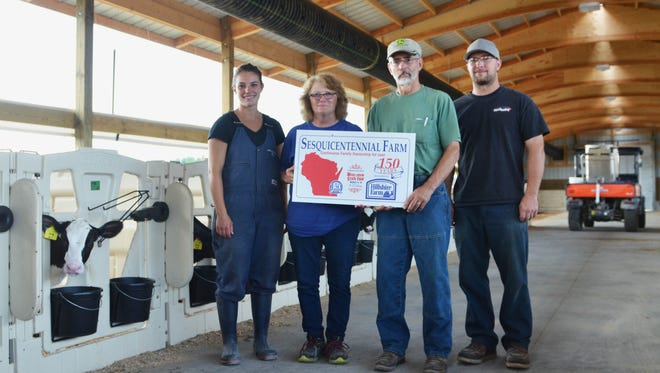 Abby, Jean, Rick and Jeremy Driscoll stand in the calf barn of Hill-Line Dairy holding a sign designating their homestead as a sesquicentennial farm.