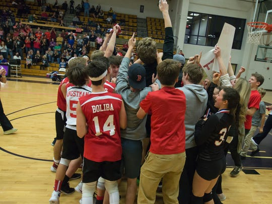 The CVU boys, pictured celebrating last year's crown, are chasing a volleyball repeat. The Redhawk girls are also aiming to defend their crown at Saturday's championships vs. Essex.