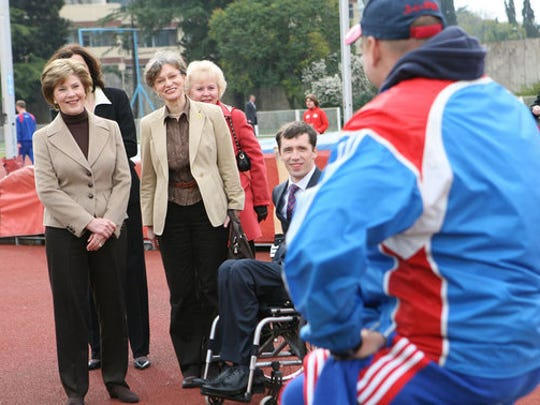 First Lady Laura Bush visits with members of the Russian Paralympic Team Sunday, April 6, 2008, during a visit to Central Sochi Stadium in Sochi, Russia. Standing with her is her interpreter, Marina Gross.