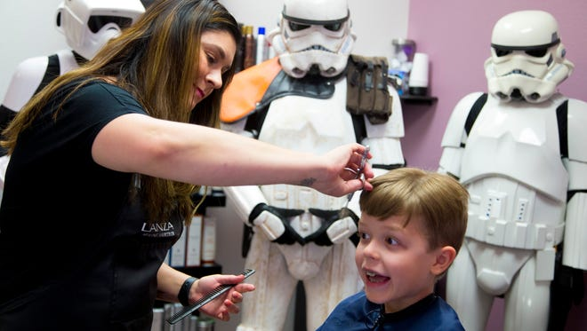 Cassie Tautimez, Pure Salon & Spa hair stylist, cuts 7-year-old Ray Decker's hair to donate to Wigs for Kids
