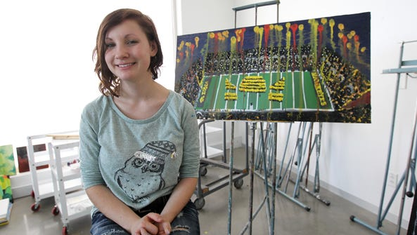Heidi Schickel poses for a photo with her painting