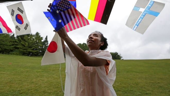 Ketrina Wonmaly, from Indonesia and now a student in Appleton, helps hang flags of countries as the 24th Annual Celebrate Diversity picnic takes place on Saturday, Aug. 20, 2016, at Memorial Park in Appleton, Wisconsin.