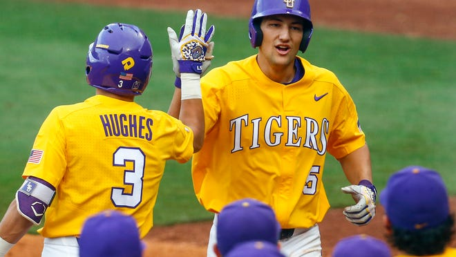 LSU's Jake Slaughter (5) celebrates with Hal Hughes (3) after he hit a two-run home run during the second inning of a Southeastern Conference tournament NCAA college baseball game against Florida, Wednesday, May 23, 2018, in Hoover, Ala. (AP Photo/Butch Dill)