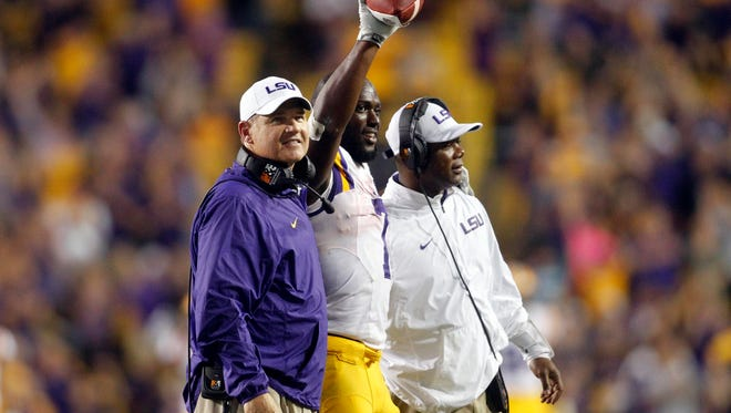 LSU Tigers running back Leonard Fournette (7) celebrates breaking the single season rushing record between head coach Les Miles and running backs coach Frank Wilson against the Texas A&M Aggies at Tiger Stadium.