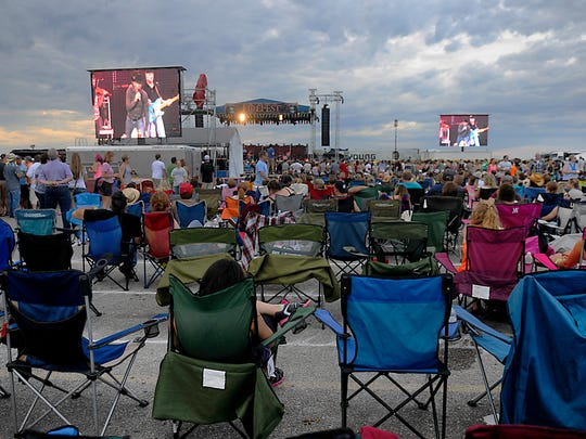 Some FireFest attendees sit in the back of the crowd in lawn chairs as a country artist performs in this Times file photo.