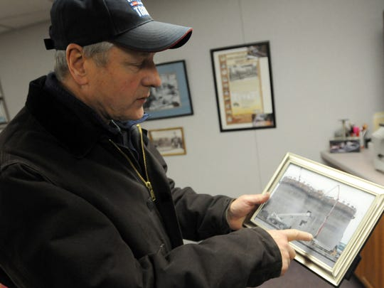 President of Port Huron Building Supply Michael Lauth points to an old photograph Monday, Feb. 15, at his office in Port Huron.