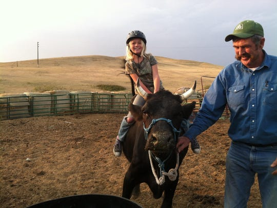 In this 2015 photo, Abby Hutton is aboard the family milk cow, Maija. Her father, Steve Hutton, helps Abby out.