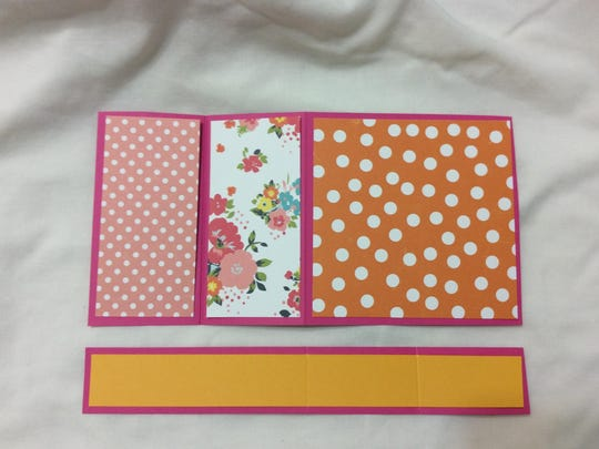On solid cardstock, paste three pieces of patterned paper. A strip of paper will go across the front once the bigger piece is folded along the patterns.