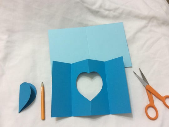 Fold your top darker-colored cardstock, scoring it at 2 and 6 inches, so that you have a center fold in you rectangle where you will center your heart cutout.