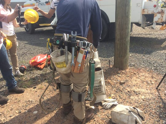 Jason Blough, a PSE&G apprentice lineman, dons his gear before climbing a utility pole. His belt with all those metal tools weighs 30 pounds or more.