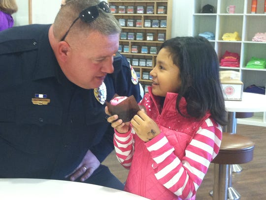 Urbandale Sgt. Gary Lang talks to Sheyla Florian, 7, of Des Moines as she prepares to eat a super power cupcake she received from Scratch Cupcakery in West Des Moines.