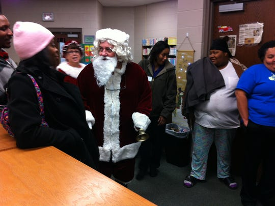 Parents of children at Isaac Lane Technology Magnet Elementary School greet Santa Claus as he enters the school library on Dec. 16.