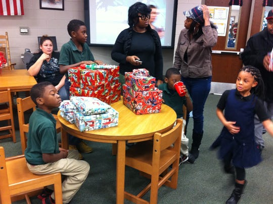 Children at Isaac Lane Technology Magnet Elementary School wait to open presents from their sponsors on Dec. 16.