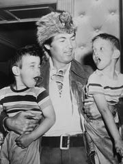 The News Sentinel reported that Andy, 4, left, and Mark Feldman, 6, got the thrill of their lives when mighty Fess Parker picked them up May 30, 1955 at the Andrew Johnson Hotel. They are the sons of Mr. and Mrs. Irving Feldman of New York City, working temporarily at Oak Ridge. (KNS Archive)