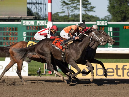 Girvin (outside), under jockey Robby Albarando, gets