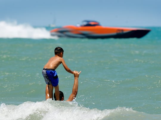 Thousands pack the shore of Cocoa Beach as offshore powerboats maneuver their way throughout rough waters during Thunder on Cocoa Beach/Space Coast Super Boat Grand Prix .