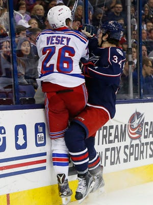 New York Rangers forward Jimmy Vesey (26) and Columbus Blue Jackets forward Josh Anderson (34) collide during the second period at Nationwide Arena.