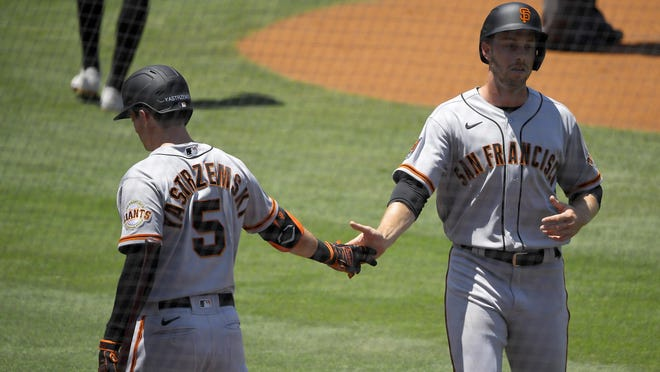 San Francisco Giants' Austin Slater, right, is congratulated by Mike Yastrzemski after scoring on a single by Darin Ruf during the first inning of a baseball game Saturday, July 25, 2020, in Los Angeles.