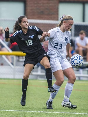 Morris Catholic senior defender Catherine Sundholm (23) directs the ball away from Parsippany Hills sophomore striker Jessica Cerrato (19) during a Morris County Tournament quarterfinal.