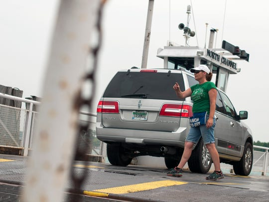 Deckhand Kim Borneman directs traffic onto the ferry Sunday, June 26, at the ferry dock in Algonac.