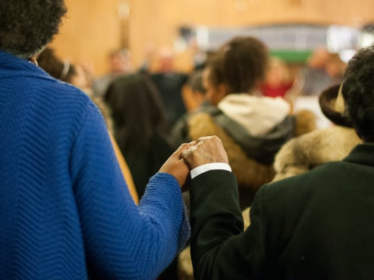 Worshipers hold hands Sunday, Jan. 8, during a Martin Luther King Jr. Celebration at the Historic Shiloh Missionary Baptist Church in Port Huron.