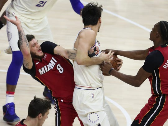 Miami's Tyler Johnson (left) gets his arm caught up with Sixer Dario Saric in the second half of the Sixers' 104-91 win in game five of an opening round playoff series at the Wells Fargo Center in Philadelphia Tuesday.