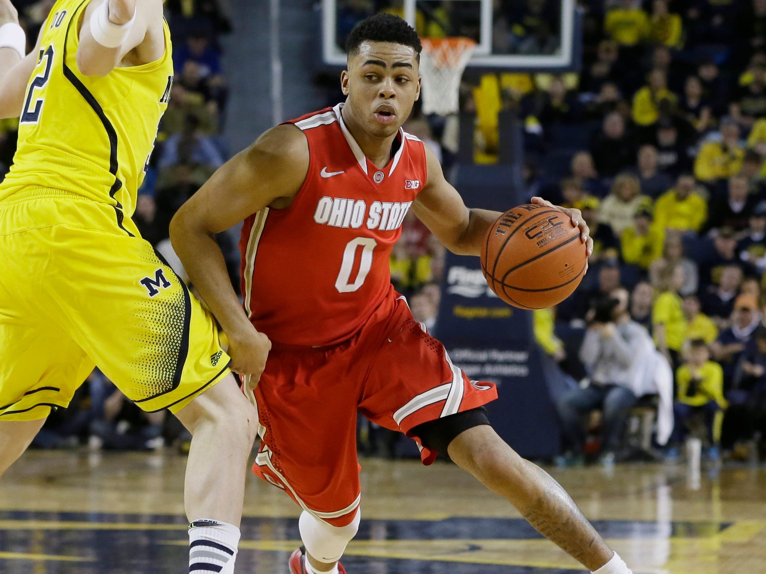 Ohio State guard D'Angelo Russell (0) drives on Michigan forward Ricky Doyle during the second half of an NCAA college basketball game earlier this season in Ann Arbor, Mich. Michigan defeated Ohio State 64-57. (
