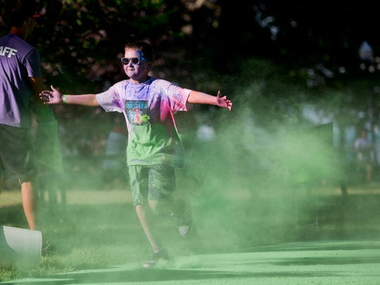 A runner holds up his arms as he is doused with color