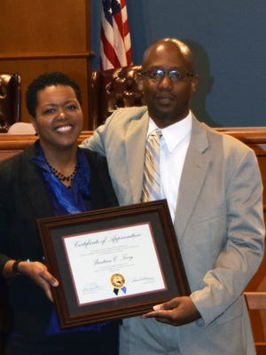 Escambia County District 3 county commissioner Lumon May awards RESTORE Advisory Committee Chairwoman Bentina Terry with a certificate of appreciation Thursday night.