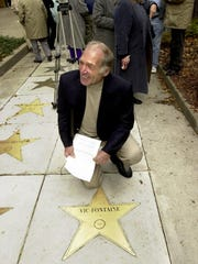 In 2004, Vic Fontaine kneels by the bronze star dedicated
