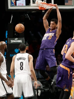 Phoenix Suns' Marquese Chriss (0) dunks in front of Brooklyn Nets' Quincy Acy, left, and Spencer Dinwiddie, center, during the first half of an NBA basketball game Thursday, March 23, 2017, in New York.